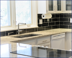 Image of kitchen with white granite countertops and black backsplash tiling with sunshine coming through window