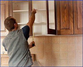 Image of man measuring the interior of a kitchen cabinet